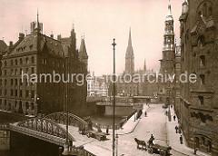 Blick über den Kannengiesserort in der Speicherstadt Hamburg - Pferdefuhrwerke fahren in den Pickhuben ein. Links der 1888 erbaute Speicherblock H, rechts ein Ausschnitt vom Lagerhaus Q. Im Hintergrund die Kirchtürme der St. Katharinenkriche.