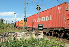 Containernzug in Hamburg Wilhelmsburg - im Vordergrund ein alter Holz Prellbock.