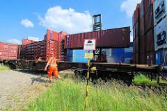 Ein Schwerlaststabler / Gabelstabler transportiert einen Container vom Containerlager zum Güterzug. Ein Arbeiter in Warnkleidung dirigiert den Stablerfahrer.
