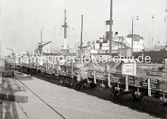 Beladenen Güterwaggons stehen am Holthusenkai; auf den Holzkisten sind die Aufschriften des Bestimmungsortes der Güter BUENOS AIRES sowie die Herkunft PRODUCCION ALEMANA zu erkennen. Zwei Hafenarbeiten stehen auf der Ladung.