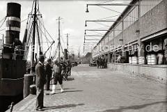 Rechts die 1937 neu gebaute Fischauktionshalle am Kai des Altonaer Fischereihafens -  Tonnen und Holzkisten zum Transport der Fische stehen auf der Laderampe des Gebäudes. Ein Pferdefuhrwerk wird beladen, dahinter ein Zugmaschine mit Anhänger.