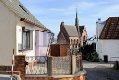 Einzelhaus mit Windfang - Baustil der 1960er Jahre; im Hintergrund die St. Bonifatius-Kirche in Bergen auf Rügen.