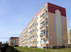 Restaurierter Plattenbau, neue Balkons - farblich dekorierte Hausfassade - Hermann-Matern-Strasse in Bergen auf Rügen.