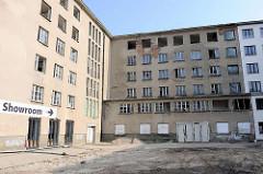 Planung zur Sanierung eines Gebäudeteils in Prora an der Ostsee - Hinweisschild zum Showroom einer vorbereiteten Eigentumswohnung in dem Gebäude.