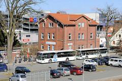 Bushaltestelle, Autobusse beim Bahnhof Buchholz i.d.N., parkende Autos.