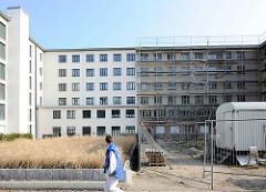 Neu + Alt; teilweise saniertes Gebäude, weisse Hausfassade - eingerüstete Fassade im Rauhputz.