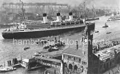 Das Passagierschiff Cap Arcona hat von den Landungsbrücken abgelegt und ist bereit zur Ausreise. Ein Schlepper befindet sich am Bug des Dampfers. Am gegenüber liegenden Elbufer die Werftanlagen mit Hellingen und Industriegebäuden.