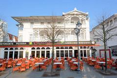 Moderner Vorbau an einer historischen Bädervilla in Binz auf Rügen; Tische mit orangenfarbenen Stühlen auf dem Fussweg - Hauptstrasse von Binz.