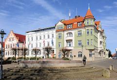 Gründerzeitarchitektur am Markt / Bergen auf Rügen - Wohnhaus mit Giebelturm, Rathaus der Stadt; blauer Himmel.