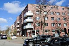 Backsteinhäuser mit weissen Eckbalkons, schnell fahrende Autos in der Sievekingallee in Hamburg Hamm.