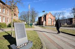 Mahnmal auf dem Gelände der Asklepios Klinik Nord-Ochsenzoll; im Hintergrund die entwidmete Anstaltskirche. Text auf der Gedenktafel; Vom Gelände dieser Klinik aus wurden während der Zeit des Nationalsozialismus 4097 Patientinnen und Patienten im Rah