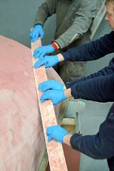 Abziehen vom frisch gespachtelten Schiffsrumpf mit einer biegsamen Leiste, mit der die überschüssige Spachtelmasse aufgenommen wird.