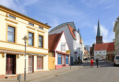 Unterschiedliche Architekturstile und farbig gestaltete Hausfassaden, Marktstrasse / Bahnhofstrasse in Bergen - im Hintergrund der Kirchturm der St. Marienkirche.