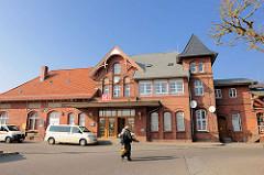 Bahnhof Sassnitz - Backsteinarchitektur; Taxis warten vor dem Eingang.
