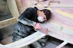 Prüfen der Gleichmässigkeit der Oberfläche beim Handschliff vom Bau eines Segelschiffs auf der Yachtwerft Lütje in Hamburg Kaltehofe / Rothenburgsort.