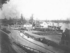 Das St. Pauli Fährhaus steht noch direkt an den St. Pauli Landungsbrücken. Auf einem Platz am Elbufer sind Karren abgestellt, mit denen die gelöschte Schiffsfracht transportiert wird. Frachtsegler liegen im Hamburger Niederhafen.