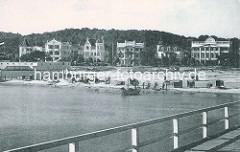 Historische Ansicht - Blick von der Seebrücke auf das Ostseeufer bei Binz; Segelboot und Standkörbe am Sandstrand - Villen in Bäderarchitektur.