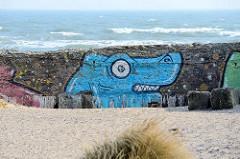 Graffiti an der verwitterten Betonmauer am Strand von Prora / Binz an der Ostsee; geplante Promenade am Wasser.