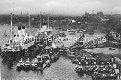 Zwei Passagierschiffe liegen an der Überseebrücke, davor haben Schlepper festgemacht. Im Hintergrund die St. Pauli Landungsbrücken mit Hafenfähren und Ausflugsschiffen.
