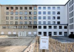 Neu + Alt; teilweise saniertes Gebäude, weisse Hausfassade - leerstehendes Gebäude, Fensterhöhlen - Fassade mit grauem Putz. Schild Privatgelände, Betreten nur für Anlieger.