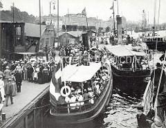 Sonntag Nachmittag auf den Anlege-Pontons der Landungsbrücken; die Ausflügler drängen sich auf den Barkassen um eine Fahrt auf der Elbe zu machen oder die Gasstätten am Elbufer z.B. Neumühlen oder Blankenese zu besuchen.