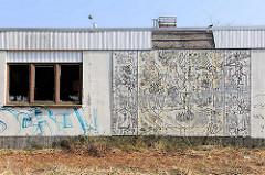 Fassadenrelief der Errungenschaften durch die sozialistische Gesellschaft an einem verlassenen Gebäude in Prora / Binz auf Rügen.