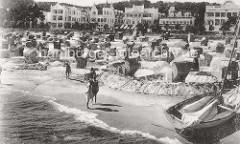 Ostseestrand in Binz auf Rügen - historisches Foto um 1900; Holzboote / Ruderboote im Verleih - Damen in Kleidern mit Hüten sitzen in Strandkörben; Villen in Bäderarchitektur / Bäderstil an der Strandpromenade.