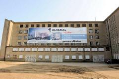 Leerstehendes Gebäudeteil der ehem. KdF-Ferienanlage Prora / Binz an der Ostsee - Werbeplakat für Eigentumapartements und Suites an der Hausfassade.