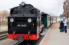 Der Zug der Rügenschen Kleinbahn kommt von Putbus und fährt in den Bahnhof Binz ein - gezogen von der Dampflokomotive 99 4633.