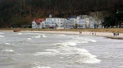 Wellen und Gischt - windiger / stürmischer Tag an der Ostsee - im Hintergrund die Strandpromenade mit Gebäuden.