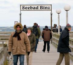 Seebrücke - Schild Seebad Binz, Urlauber mit warmen Jacken und Mützen - windiger Frühlingstag.