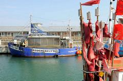 Rote Fahnen an Bord eines Fischkutters im Hafen von Sassnitz auf der Insel Rügen - die roten Flaggen markieren die ausgebrachten Fischernetze in der Ostsee.