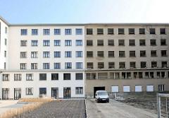 Neu + Alt; teilweise saniertes Gebäude, weisse Hausfassade - leerstehendes Gebäude, Fensterhöhlen - Fassade mit grauem Putz.