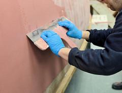 Auftragen der Epoxidspachtelmasse mit einem Spachtel auf den Schiffsrumpf.
