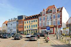 Restaurierte Wohnhäuser / Geschäftshäuser am Markt von Bergen auf Rügen; Parkplatz, parkende Autos / PKW.