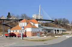 Restaurierter Güterbahnhof im Hafen von Sassnitz - dahinter die Fussgänger Hängebrücke, die 2007 eingeweiht wurde und vom Rügenplatz beim alten Kurhaus zum Stadthafen führt.  Die Brücke wurde vom Ingenieurbüro Schlaich, Bergermann und Partner entworf