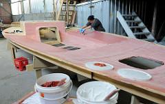 Auftragen der Epoxidspachtelmasse mit einem Spachtel auf den auf das Schiffsdeck.
