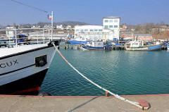 Bug eines Schiffs, vertäut an der Mole im Sassnitzer Hafen - im Hintergrund Fischkutter.