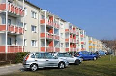 Sanierte Plattenbauten - Neubauten mit roten Balkonverkleidungen am Karl-Liebknecht-Ring in Sassnitz; schräg parkende Autos.
