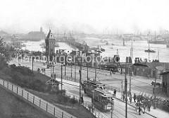 St. Pauli Landungsbrücken ca. 1900 - zwei Strassenbahnen an der Haltestelle Landungsbrücken; ein Arbeiter trägt mehrere Milchkannen, ein anderer transportiert ein Fass auf der Handkarre. Leere Karren sind an der Strasse abgestellt.