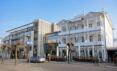 Neu + alt; weisse Bädervilla mit Holzschnitzerein am Balkon - moderner Neubau mit verglaster Verbindung.