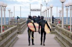 Seebrücke Binz - Surfer mit Surfbrett gehen zum Surfen im 4 Grad warmen Ostseewasser - Frühling an der Ostseeküste.