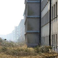 Leerstehende Gebäude - KdF Ferienanlage Prora auf Rügen / Ostsee. Im Hintergrund sanierte Teile der ehem. Ferienanlage, jetzt Eigentumswohnungen mit Balkons.