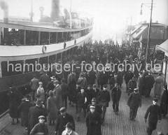 Hafenarbeiter verlassen ein Fährschiff an den Hamburger Landungsbrücken. ( ca. 1926 )