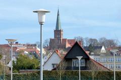 Laternen / Lampen auf einem Parkplatz in Bergen - im Hintergrund der Kirchturm der St. Marien-Kirche in Bergen auf Rügen.
