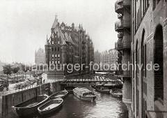 Blick in das Wandrahmsfleet auf die Brücke der Holländischen Reihe (Dienerreihe) - offene und abgedeckte Schuten liegen auf dem Wasser an den Kaimauern oder unter dem Lagergebäude des Speicherblocks W. Auf der Strasse stehen Handkarren und P