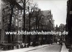 der alte Wandrahm im Gebiet der der zukünftigen Hamburger Speicherstadt - die Strasse ist mit Kopfstein gepflastert, ein Pferdewagen mit Kisten beladen steht am Strassenrand. Leere Karren / Schottsche Karren sind auf einem Hof abgestellt.