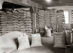 Der Kaffee aus Kolumbien ist in Jutesäcke vernäht und bis an die Decke des Speicherbodens gestapelt. Die Säcke tragen die Aufschrift Produkt of Colombia - 70 Kilos. Ein Haufen Kaffee ist auf dem Lagerboden ausgeschüttet.