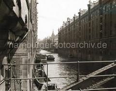 Blick von der Kehrwiederstegbrücke auf das Brooksfleet; Schuten und Barkassen liegen an der Gebäudemauer des Speichergebäudes Block D. Die Kaffeeladung eines der Kähne wird gerade gelöscht.