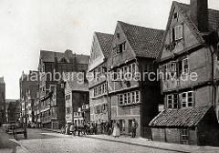 Wohngebäude am Brooksgraben - die Einwohner der historischen Fachwerkhäuser stehen auf dem gepflasterten Fussweg. Die Frauen und Mädchen tragen weisse Schürzen - auf der Strasse sind Handwagen und Karren abgestellt.